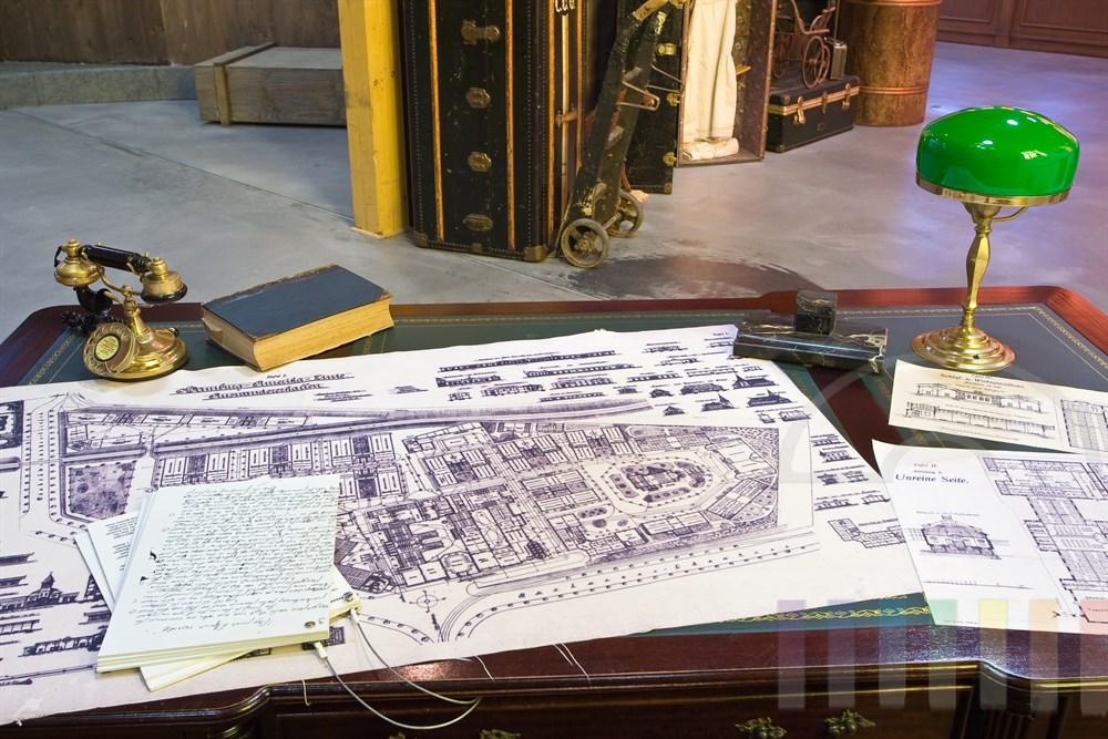 Nachbau von Albert Ballins Schreibtisch mit ausgebreiteten Bauplänen der Auswandererstadt auf der Veddel