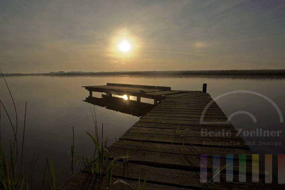 Kurz nach Sonnenaufgang am Angelsteg eines Sees auf Sylt