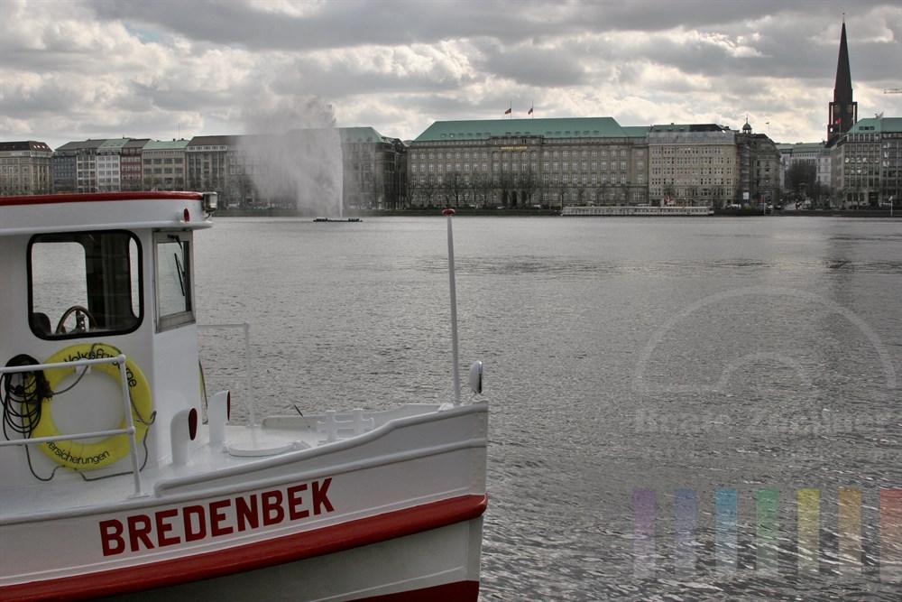 """Alsterschiff """"Berdenbek"""" liegt am Neuen Jungfernstieg, Blick über die Binnenalster Richtung Ballindamm mit Hapag-Lloyd-Gebäude. Alsterfontäne ist in Betrieb"""