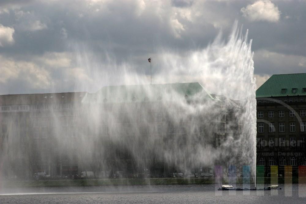 Alsterfontäne auf der Hamburger Binnenalster schiesst Wassersalven in die Luft, im Hintergrund Bürohäuser am Ballindamm