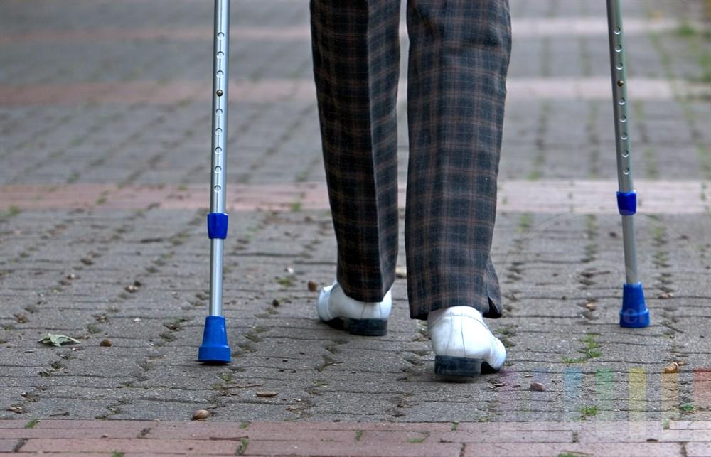 Beine mit Gehhilfen auf gepflastertem Weg