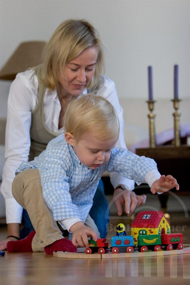 Mutter sitzt mit ihrem kleinen Sohn (2 Jahre) auf dem Fußboden und spielt mit ihm gemeinsam mit der Holzeisenbahn