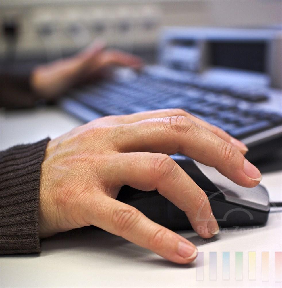 Nahaufnahme: Rechte Frauenhand umfasst eine Computermaus, die andere tippt auf Tastatur. Das Foto entstand unter realen Arbeitsbedingungen in einem Callcenter