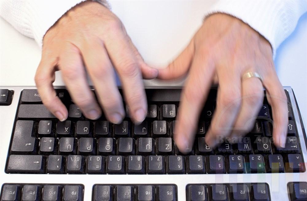Finger einer Frauenhände tippen im 10-Finger System auf einer Computer-Tastatur. Das Foto entstand unter realen Bedingungen in einem Callcenter.