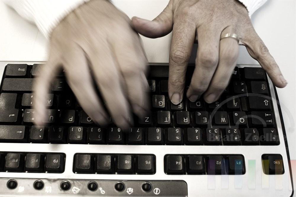 Finger einer Frauenhände tippen im 10-Finger System auf einer Computer-Tastatur. Das Foto entstand unter realen Bedingungen in einem Callcenter. Das Foto wurde am PC farbentsättigt.
