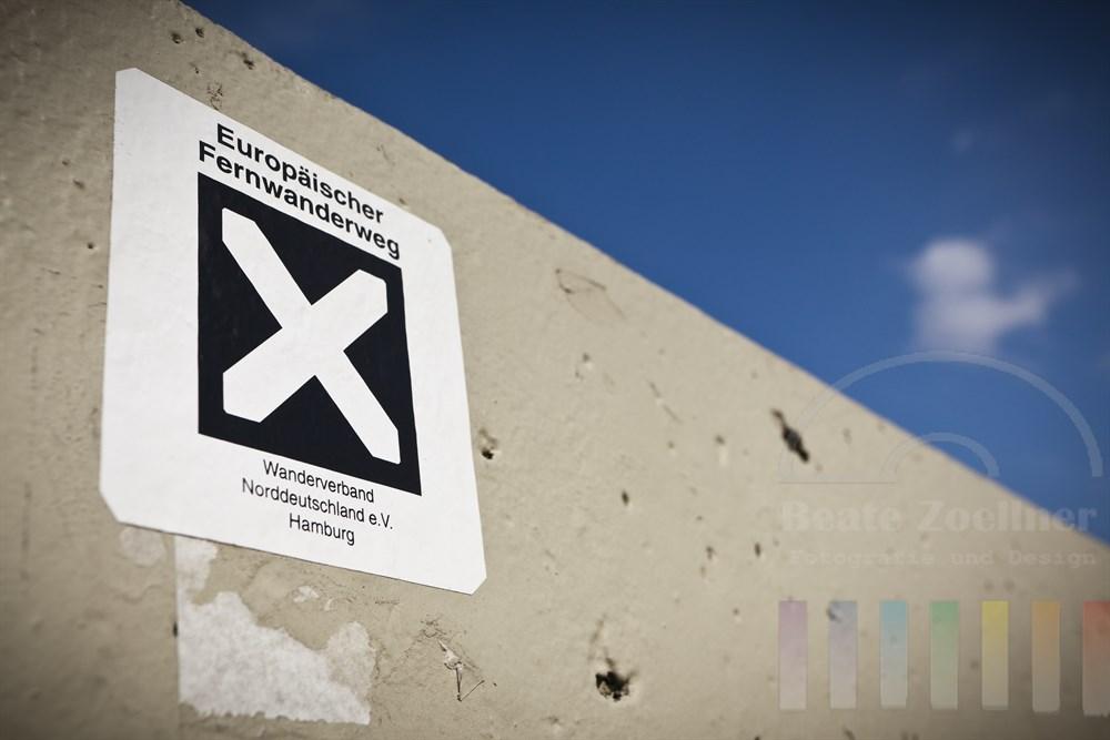 Hinweisschild auf den Europaeischen Fernwanderweg an einer Betonmauer am Hamburger Stintfang