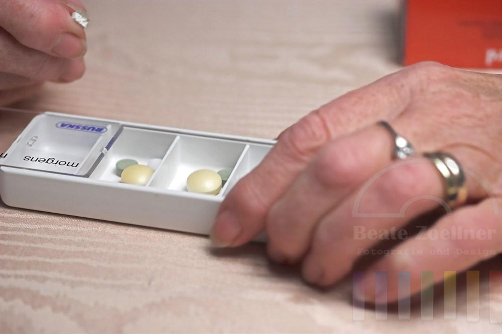 """Haende einer aelteren Frau halten Kaestchen, in das sie mit der rechten Hand eine halbierte Tablette legt. Da Plastik-Kaestchen ist in vier Faecher mit den Aufschriften """"morgens"""", """"mittags"""", """"abends"""" und """"nachts"""" eingeteilt. Unter den Tabletten sind Schmerzmittel wie Morphium und ein Mistel-Präparat (gruene Tablette mit eingestanztem """"W""""), das zur Mistel-Therapie bei Krebs-Erkrankungen verabreicht wird."""