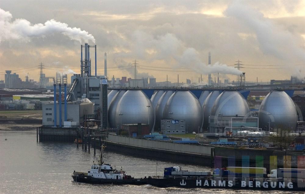 Blick vom hoeher gelegenen Elbufer über den Fluss zu den Faultuermen der Hamburger Stadtentwaesserung. Auf der Elbe faehrt ein Lastkahn beladen mit LKW, im Hintergrund stossen Schornsteine ihre Emissionsschwaden in den bedeckten Himmel