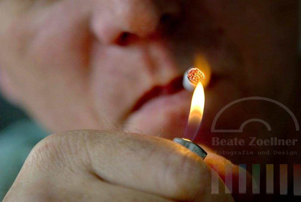 Nahaufnahme: Mann zündet sich selbstgedrehte Zigarette mit Feuerzeug an, Flamme, Zigarette glimmt, Hand im Vordergrund