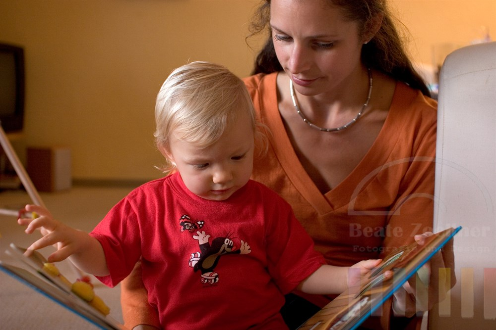 Mutter sitzt mit ihrer Tochter (ca. 18 Monate alt) auf dem Fußboden. Die beiden schauen zusammen ein großes, buntes Bilderbuch mit dreidimensionalen Elementen an