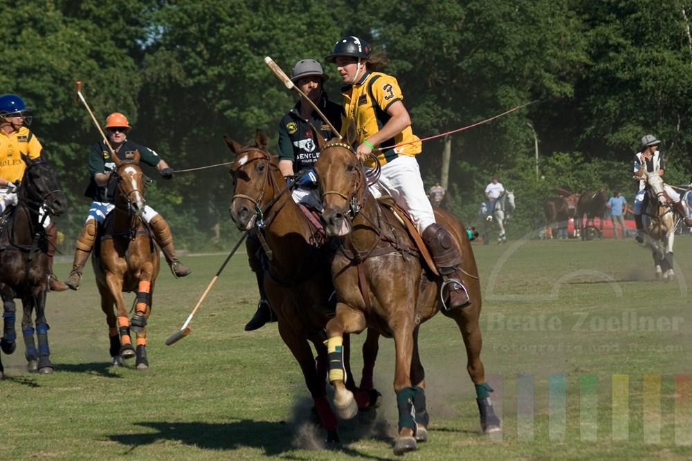 Zweikampfszene beim Polo, zwei Spieler gegnerischer Mannschaften galoppieren seitlich auf Kamera zu, Staub wirbelt auf