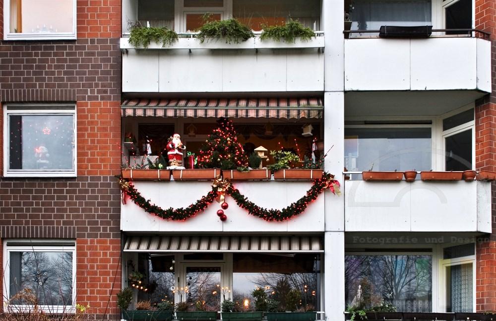 Hochhausfassade mit mehreren Balkonen. Einer der Balkone ist überladen mit weihnachtlicher Dekoration