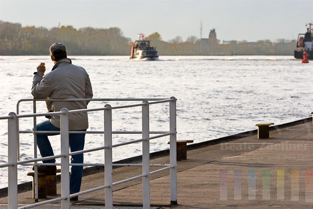 Mann steht laessig am Schiffsanleger in Hamburg-Oevelgoenne und wartet auf die Faehre, die vom anderen Elbufer heran naht, tiefstehende Sonne, Gegenlicht