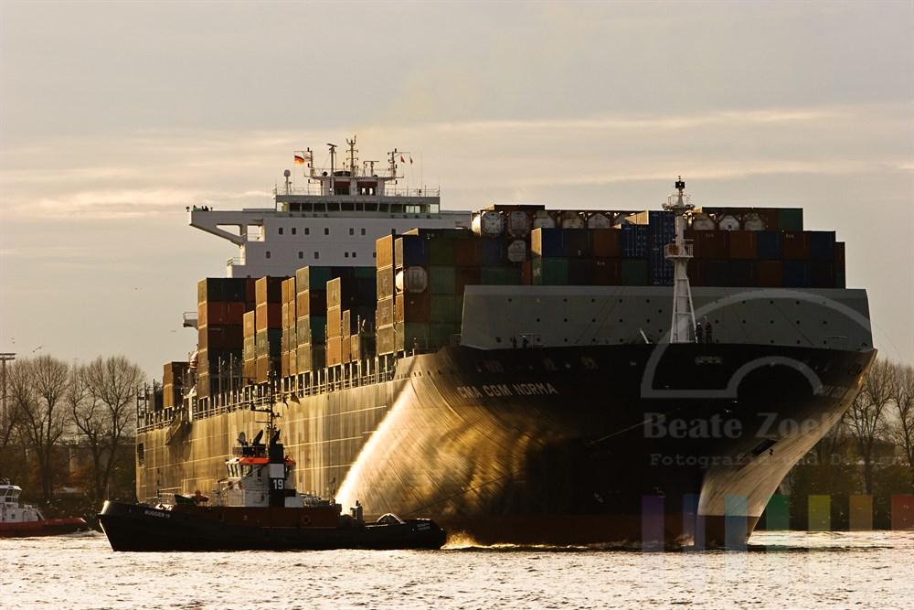 riesiges Containerschiff wird von Schleppern auf der Elbe gedreht, Abendstimmung bei tiefstehender Sonne