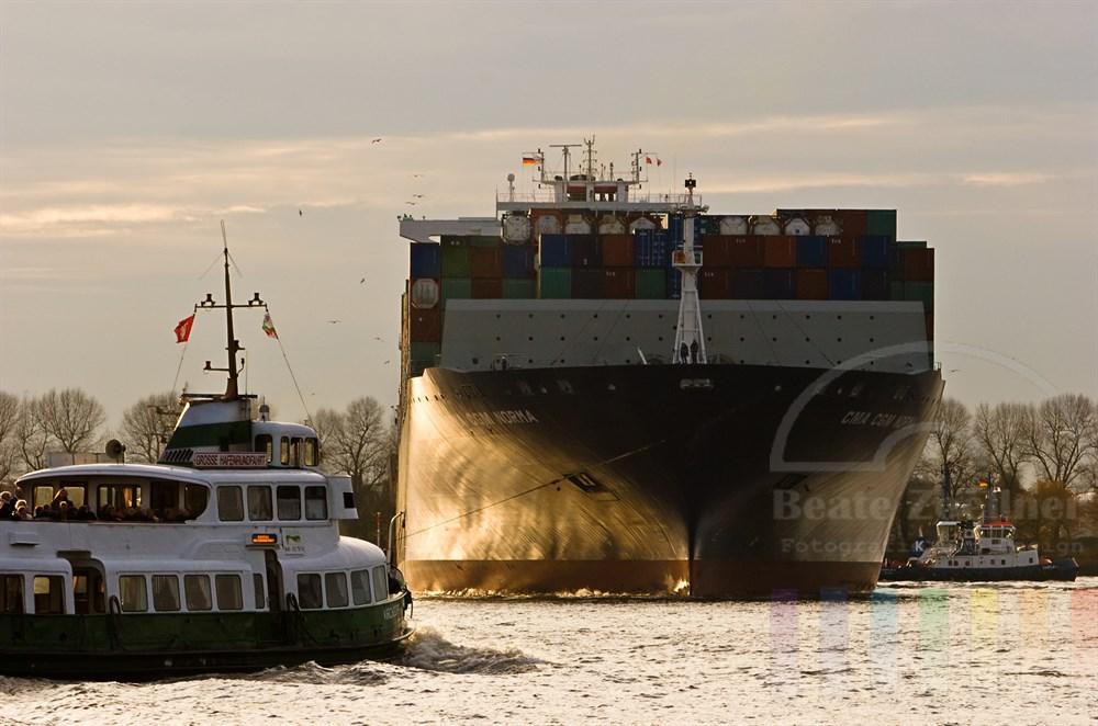 riesiges Containerschiff wird von Schleppern auf der Elbe gedreht waehrend ein Hafenrundfahrtsboot passiert, Abendstimmung