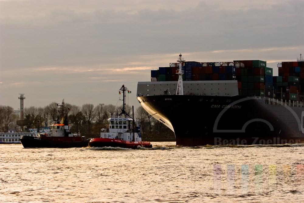 zwei Schlepper ziehen ein riesiges Containerschiff ueber die Elbe in Richtung Hamburger Hafen, Abendstimmung,