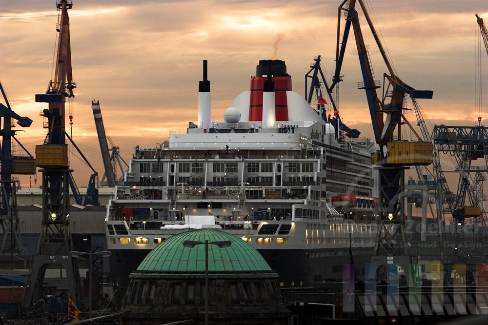 """Das Luxus-Kreuzfahrtschiff """"Queen Mary 2"""" liegt im Dock bei Blohm & Voss. Arbeiter wuseln wie Ameisen auf den Decks des riesigen Schiffes umher, Kräne flankieren es. Im Vordergrund ist eine Kupfer-Kuppel der Hamburger Landungsbrücken zu sehen, Abendhimmel"""