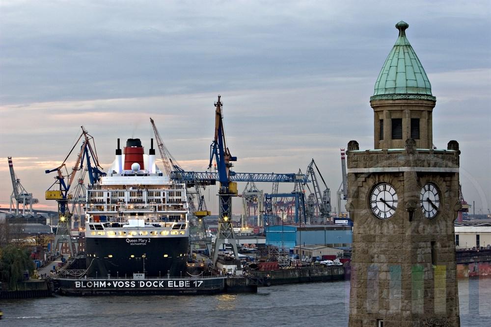 """Fotografiert im letzten Tageslicht: Das Kreuzfahrtschiff """"Queen Mary 2"""" liegt im Dock der Hamburger Werft Blohm & Voss. Im Vordergrund der Pegelturm der Hamburger Landungsbrücken"""