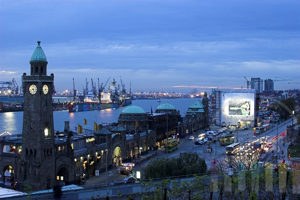 Blick in der Abenddämmerung über die Hamburger Landungsbrücken, die Elbe und die Docks des Hafens. Im Vordergrund fliesst der Feierabendverkehr auf der Straße. Unter einer Plane wird das Kuppelgebäude des Alten Elbtunnels restauriert.