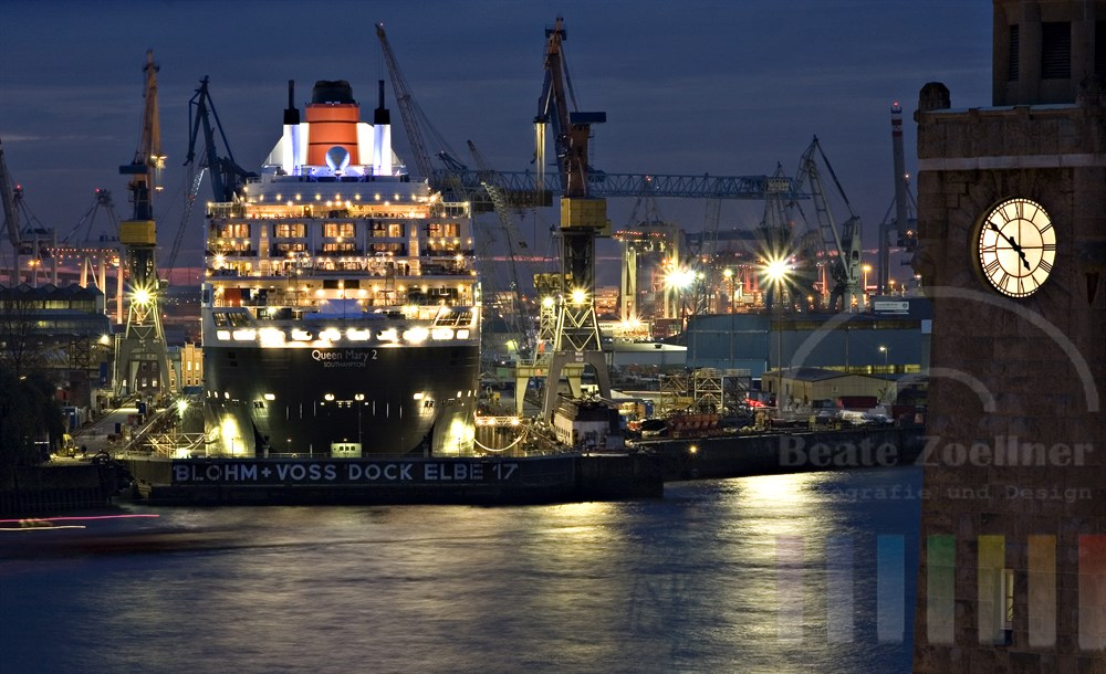 """Zur Blauen Stunde: Das Kreuzfahrtschiff """"Queen Mary 2"""" liegt im Dock der Hamburger Werft Blohm & Voss. Im Vordergrund der Pegelturm der Hamburger Landungsbrücken"""