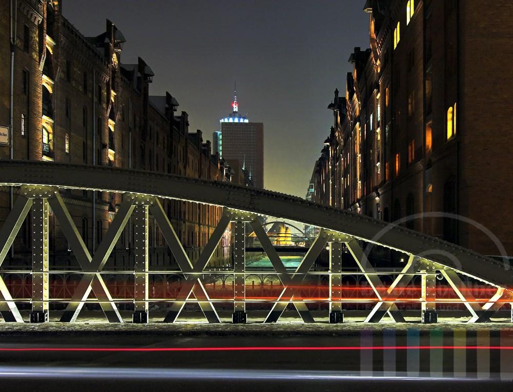 Blick in die nächtliche historische Speicherstadt, den Vordergrund bildet der stählerne Bogen der Sandbrücke, Rücklichter eines vorbeifahrenden Autos bilden einen roten Streifen.