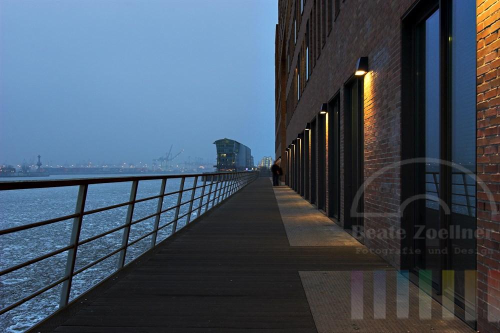 Abenddämmerung: Moderne Architektur am Ufer der Elbe in Hamburg-Altona. Auf der Elbe schwimmen Eisschollen. Zwei Passanten schlendern auf der Promenade entlang.
