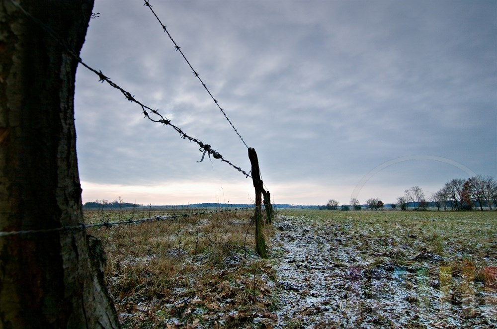 Ausblick auf leicht verschneite Weiden, begrenzt durch einen Stacheldrahtzaun. Fotografiert bei Lentföhrden, Kreis Segeberg, Schleswig-Holstein
