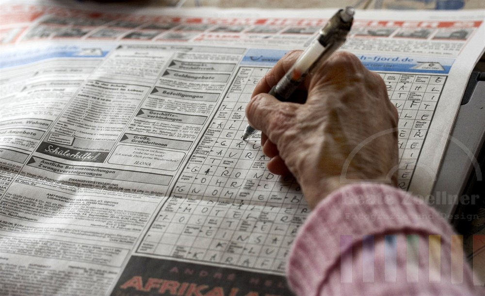 Hand einer Seniorin haelt Schreiber und fuellt Buchstaben in Tageszeitungs-Kreuzwortraetsel ein