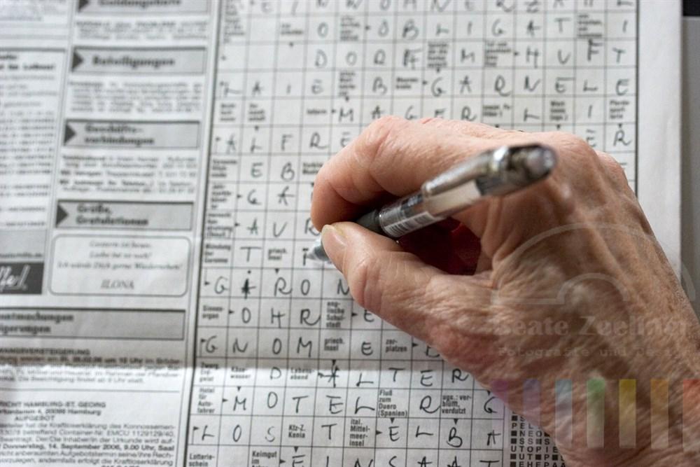 Hand einer Seniorin haelt Schreiber und fuellt Buchstaben in Tageszeitungs-Kreuzwortraetsel ein, close