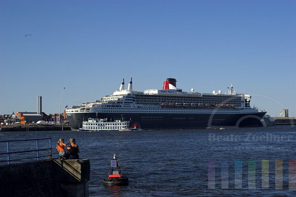 """Das Luxus-Kreuzfahrtschiff """"Queen Mary 2"""" liegt bei schönstem Sommerwetter am Kreuzfahrtterminal im Hamburger Hafen.  Eine Frau und ein Mädchen sitzen am gegenüber liegenden Elbufer auf einer Kaimauer und schauen auf das riesige Schiff."""