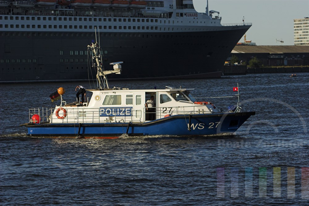 """Boot der Hamburger Wasserschutzpolizei kreuzt bei schönstem Sommerwetter im Hafen vor der Bordwand des riesigen Luxus-Kreuzfahrtschiffes """"Queen Mary 2"""""""