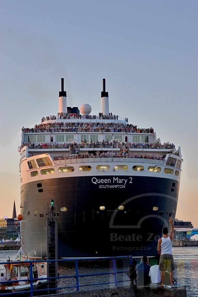 """Heck des Kreuzfahrtschiffes """"Queen Mary 2"""" beim Wendemanöver im Hamburger Hafen. Zahlreiche Menschen hatten sich auch auf der anderen Elbseite eingefunden, um bei schönstem Sommerwetter den Auslaufen des Schiffes zuzuschauen."""