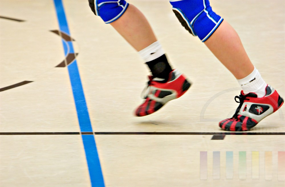 Symbolfoto: Beine einer jungen Handballspielerin in Bewegungsunschärfe laufen über den Boden einer Sporthalle