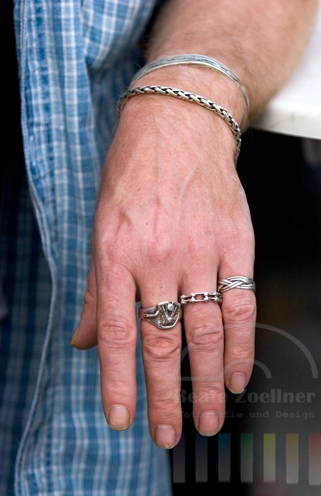 Mit silbernen Ringen und Armbändern geschmückte Hand und Unterarm eines Mannes hängt lässig über eine Tischkante.