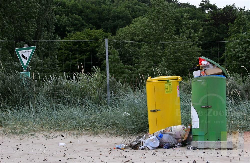 überfüllte Mülltonnen stehen an einem Zaun, direkt dahinter beginnt das durch ein entsprechendes Schild gekennzeichnete Naturschutzgebiet