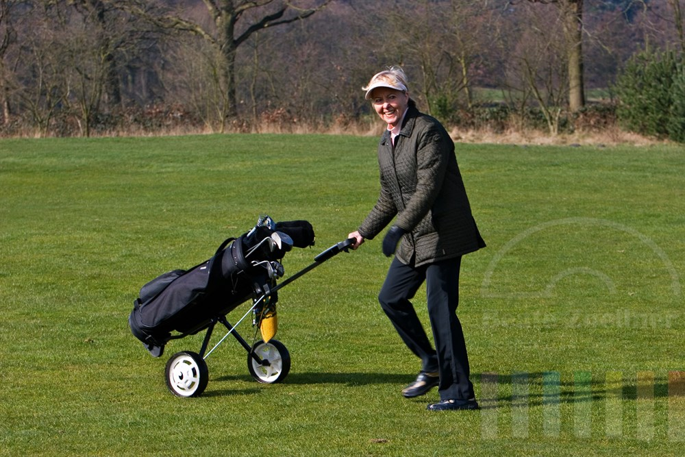 Portrait: Seniorin (72 Jahre) in sportlichem Outfit schiebt lächelnd ihren Caddy über den frühlingshaften Golfplatz