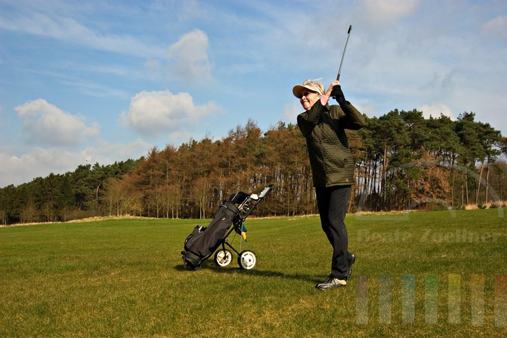 Seniorin (72 Jahre) spielt Golf auf einem frühlingshaften Platz, blauer Himmel, Sonnenschein
