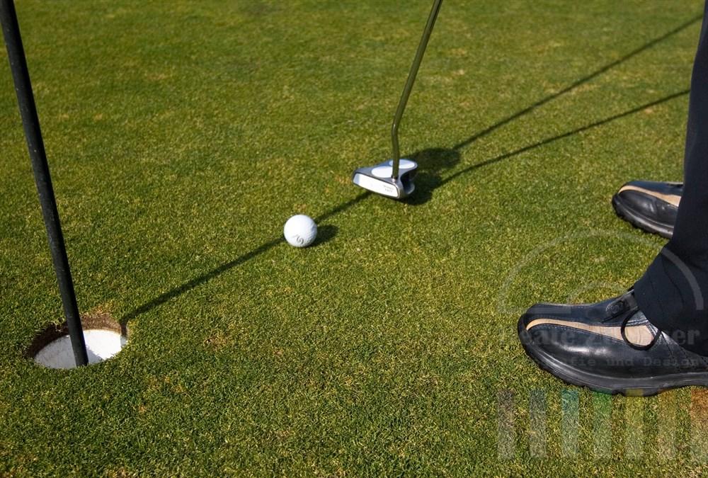 Golfball läuft kurz nachdem er vom Schläger getroffen wurde geradewegs auf das Loch zu. Golfschuhe und Bein des Spielers im Anschnitt