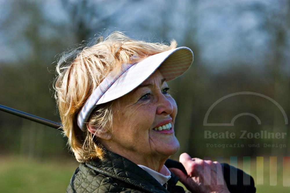 Portrait: Seniorin (72 Jahre) spielt Golf, zufrieden lächelnd schaut sie dem eben geschlagenen Ball hinterher, den Schläger hat sie geschultert