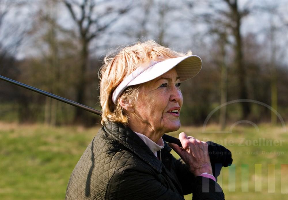 Portrait: Seniorin (72 Jahre) spielt Golf. Nach dem Schlag schaut sie dem fliegenden Ball zufrieden lächelnd hinterher