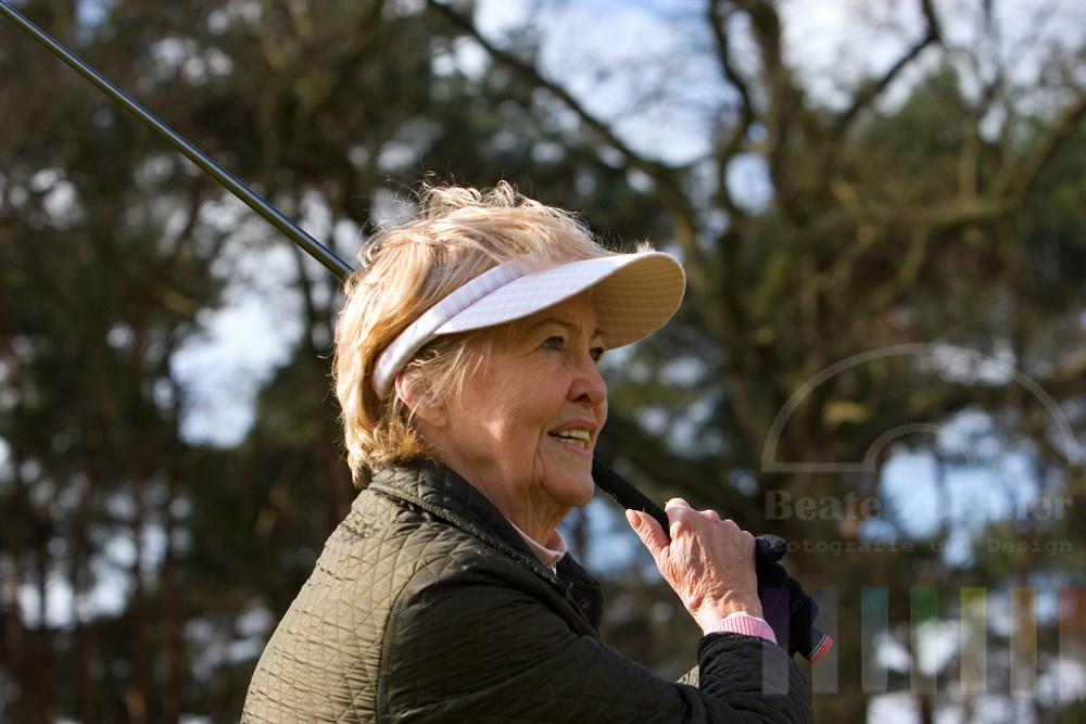 Portrait: Seniorin (72 Jahre) spielt Golf. Nach dem Schlag schaut sie dem fliegenden Ball hinterher