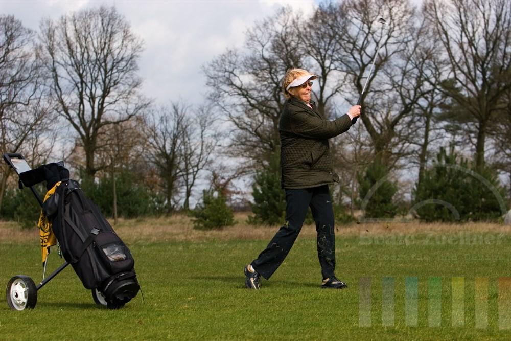 Seniorin (72 Jahre) spielt Golf. Gerade hat sie mit viel Kraft einen Ball geschlagen, die Grashalme fliegen durch die Luft