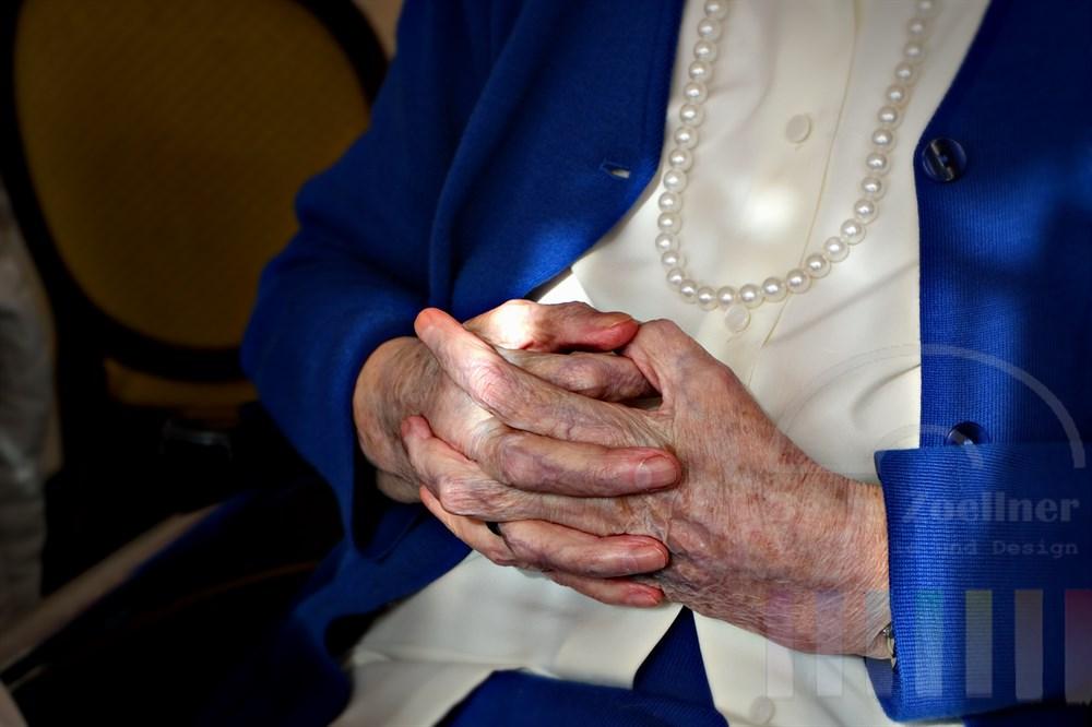 Sitzende alte Dame hält ihre Hände gefaltet im Schoss. Sie ist fein gekleidet mit einem Strickkostüm und träge eine Perlenkette