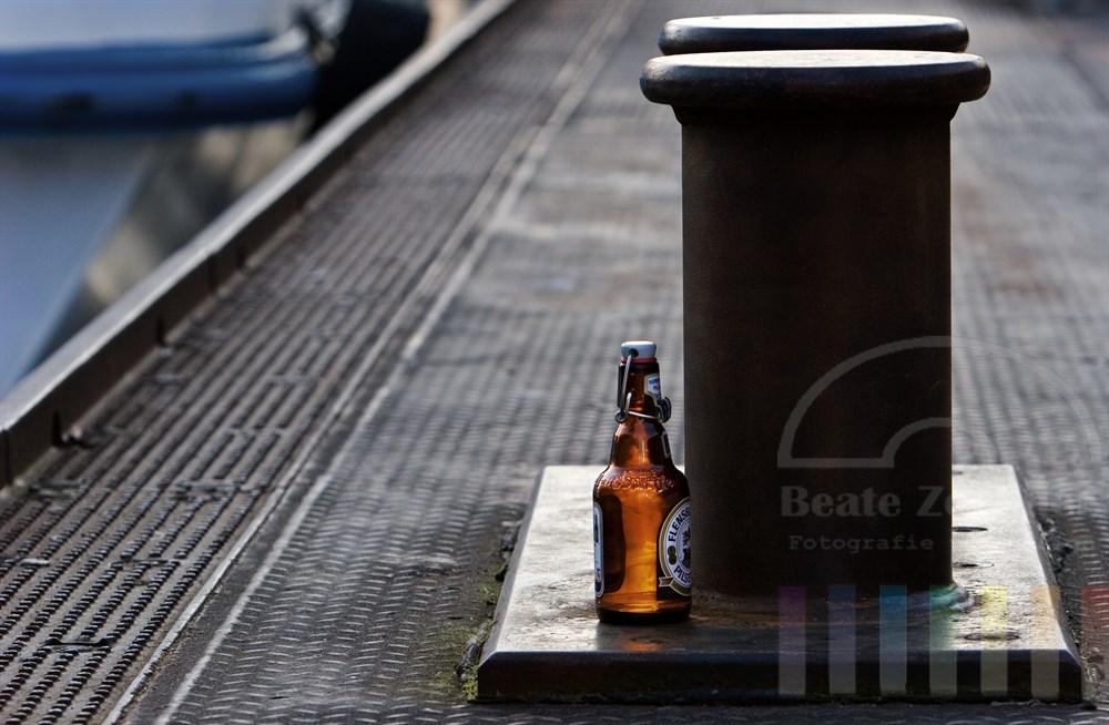 Leere Bierflasche steht an einem Poller auf den Hamburger Landungsbrücken