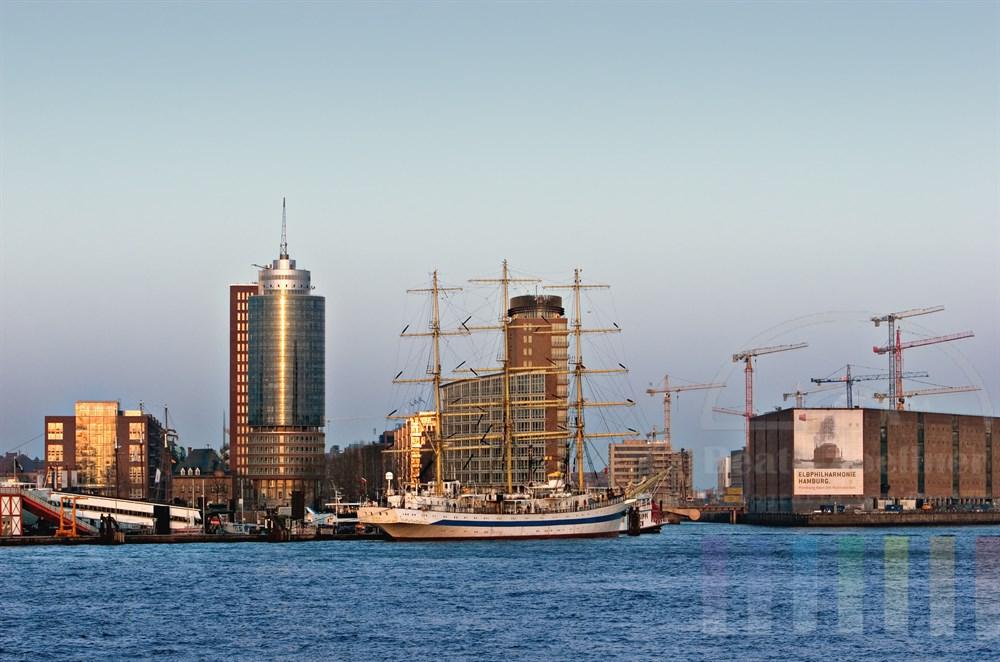 """Abendstimmung: Blick auf die Hamburger Hafenkulisse mit dem Segelschiff """"Mir"""",  dem Hanseatic Trade Center, dem Kaispeicher A, der zur Elbphilharmonie umgebaut wird und der Grossbaustelle Hafencity"""
