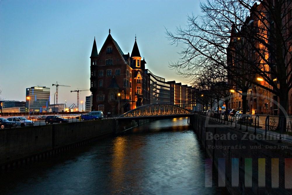 """Blaue Stunde: Beleuchtetes historische Gebäude in der Hamburger Speicherstadt an der Neuerwegsbrücke, im Hintergrund entsteht das Projekt """"Hafencity""""- ein neuer Stadtteil Hamburgs"""