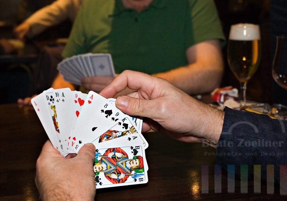 Männerhand hält Skatkarten, im Hintergrund ist Mitspieler, ein Bierglas steht auf dem Tisch, Kneipenatmosphäre