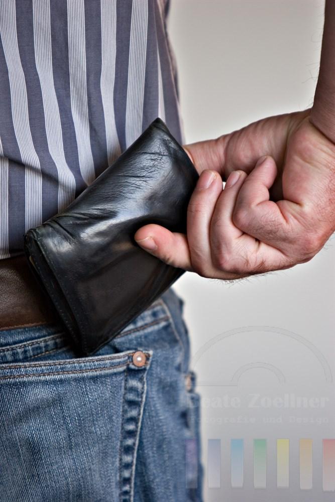 Mann zieht Brieftasche aus der Gesässtasche seiner Jeans - typisch Mann!