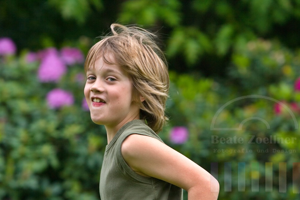 kleiner Junge (8 Jahre) mit frechem Lachen rennt durch Garten, seine Haare wehen im Wind