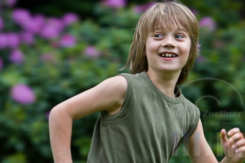 Kleiner Junge (8 Jahre) rennt mit wehenden Haaren lachend durch einen Garten, sein Blick geht über die Schulter nach hinten zu seinem Verfolger